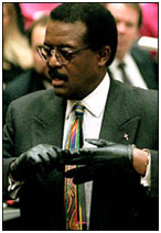 Johnny Cochran trying on glove in court